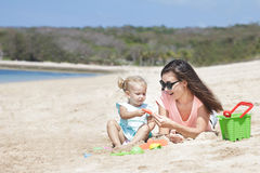 Little baby girl playing sand toys with her mother at the beach Stock Photography