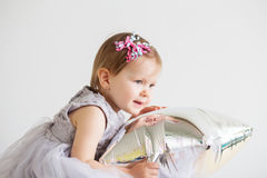 Little baby girl playing with silver star-shaped balloon. Stock Images