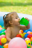 The little baby girl playing with toys in inflatable pool in the summer sunny day Stock Photography