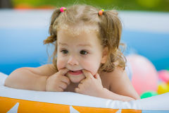 The little baby girl playing with toys in inflatable pool in the summer sunny day Stock Photo