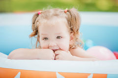 The little baby girl playing with toys in inflatable pool in the summer sunny day Stock Photos