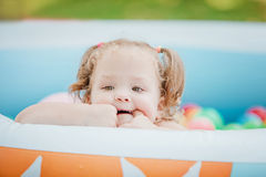 The little baby girl playing with toys in inflatable pool in the summer sunny day Stock Images