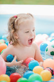 The little baby girl playing with toys in inflatable pool in the summer sunny day Stock Image