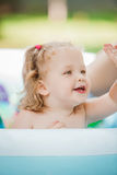 The little baby girl playing with toys in inflatable pool in the summer sunny day Royalty Free Stock Photography