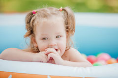 The little baby girl playing with toys in inflatable pool in the summer sunny day Royalty Free Stock Photos