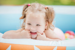 The little baby girl playing with toys in inflatable pool in the summer sunny day Royalty Free Stock Photo