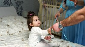 Little baby girl plays with a balloon sitting on the bed stock footage