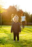 Little baby girl plays in the park in backlight. Stock Image