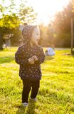Little baby girl plays in the park in backlight. Stock Photo