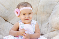 Little baby girl poses on a white chair.  She is smiling happily Stock Images