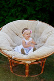 Little baby girl poses on a white chair.  She is smiling happily Royalty Free Stock Photos