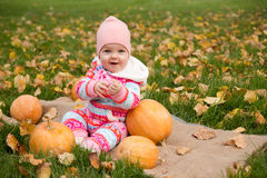 Little baby girl with pumpkins Royalty Free Stock Image