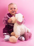 Little baby girl in purple dress with a toy Stock Photo