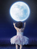 Little baby girl reaching to the moon Royalty Free Stock Image