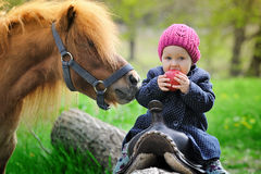 Little baby girl with red apple and pony Royalty Free Stock Photography