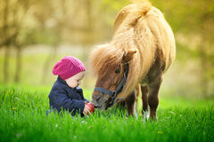 Little baby girl with red apple and pony. In spring park Stock Photography