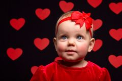 Little baby girl in a red dress on a dark background with red he Stock Photos