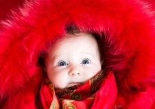 Little baby girl in a red fur jacket Stock Images