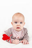 Little baby girl with red heart on a stick. Portrait of sweet little baby girl holding red heart on a stick valentines day symbol Royalty Free Stock Photo