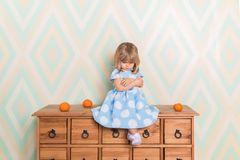Little baby girl in room sitting cross-legged and cross-arms on chest of drawers with tangerines on rhomb wallpaper royalty free stock photography