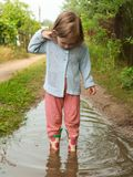 A little baby girl in rubber boots exploring the world and the depth of the puddles royalty free stock images