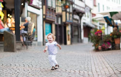 Little baby girl running in a beautiful street Stock Image