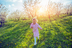 Little baby girl that runs between flowering trees at sunset. Ar Royalty Free Stock Photos