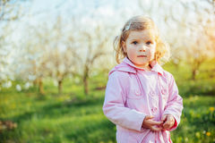 Little baby girl that runs between flowering trees at sunset. Ar Royalty Free Stock Images