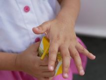 Little baby girl`s hands learning to put the straw into milk box by herself royalty free stock photography