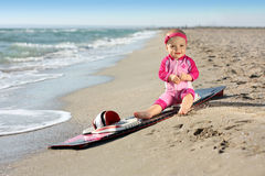Little baby girl on the sand beach with surf board Stock Photos
