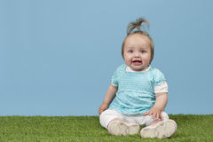 Little baby girl seated on grass Stock Photos