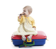 Little baby girl seated on a red and blue suitcas Royalty Free Stock Photos