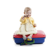 Little baby girl seated on a red and blue suitcas Stock Images