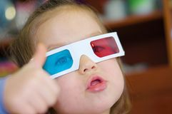 Little baby girl showing super in 3D anaglyph cinema glasses for stereo image system with polarization. 3D goggles with red and bl. Little baby girl showing royalty free stock images