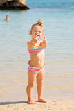 Little baby girl showing thumbs up on beach. Stock Photo