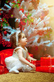 Little baby girl sit under the Christmas tree with a lot of gift Stock Image