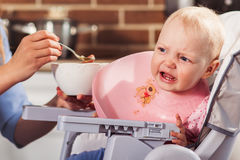Little baby girl sits in high chair and feeding with spoon her beautiful mother Stock Images