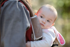 Little baby girl sitting in a baby carrier Royalty Free Stock Image