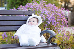 Little baby girl sitting on a bench next to a violet flower bush Royalty Free Stock Image