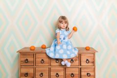 Little baby girl sitting cross-legged on chest of drawers holding tangerine in hand and pointing down with index finger royalty free stock photo