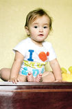 Little baby girl sitting on the dresser Royalty Free Stock Photography