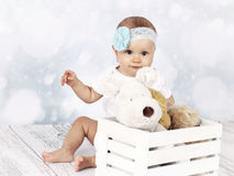 Little baby girl sitting on the floor with box of plush toys Royalty Free Stock Image