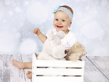 Little baby girl sitting on the floor with box of plush toys Stock Image