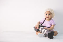 Little baby girl sitting on the floor holding dslr camera Royalty Free Stock Photo