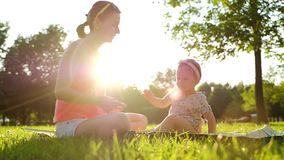 Little baby girl sitting with her mother on green grass in summer. stock footage