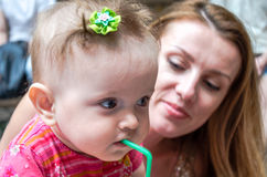 Little baby girl sitting on her mother hands in a cafe at a party and drink a cocktail through a straw from a glass Stock Photography