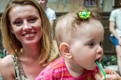 Little baby girl sitting on her mother hands in a cafe at a party and drink a cocktail through a straw from a glass Stock Images