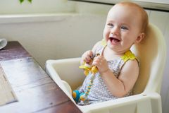Little baby girl sitting in high chair in cafe. Restaurant or at home royalty free stock image