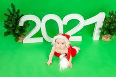 Little baby girl sitting on a red sled in a Santa hat on a white isolated background with a snowman, happy new year 2021, space