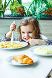 Little baby girl sitting in the restaurant or cafe and eating food. Stock Photography